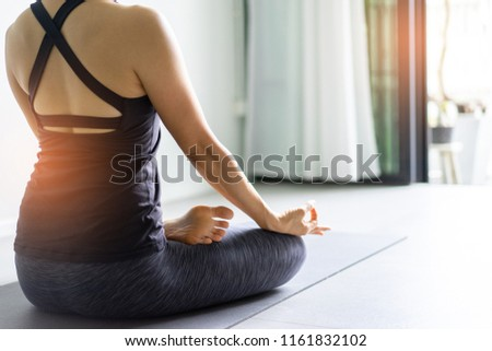 Young woman practicing yoga in  gray background.Young people do yoga indoor.Close up hands in meditating gesture. Copy space. #1161832102