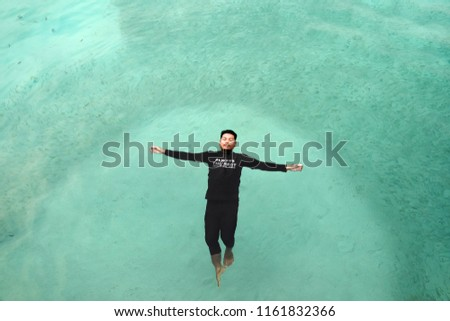Perhentian  Island , Malaysia - August 15th, 2018 :Top view of sea diver  in a water suit is swimming with   fish #1161832366