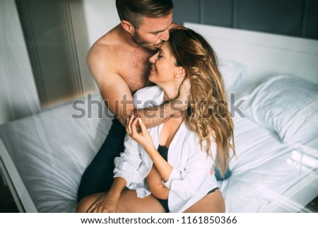 Attractive couple sharing intimate moments in bedroom #1161850366