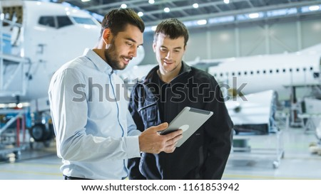Aircraft Maintenance Worker and Engineer having Conversation. Holding Tablet. #1161853942
