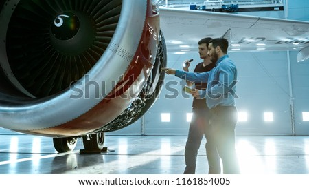In a Hangar Aircraft Maintenance Engineer Shows Technical Data on Tablet Computer to Airplane Technician, They Diagnose Jet Engine Through Open Hatch. They Stand Near Clean Brand New Plane. #1161854005