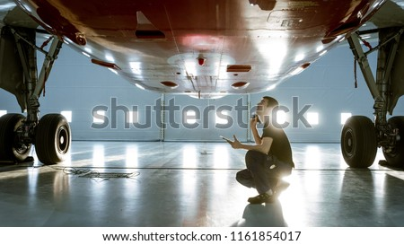 In a Hangar Aircraft Maintenance Young Engineer/ Technician/ Mechanic With Tablet Computer Inspects Airplane Jet Engine. He Opens Engine Hatch and Examines Insides with a Flashlight. Royalty-Free Stock Photo #1161854017