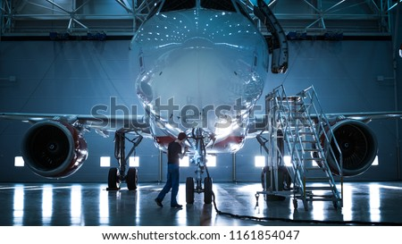 Brand New Airplane Standing in a Aircraft Maintenance Hangar while Aircraft Maintenance Engineer/ Technician/ Mechanic goes inside Cabin via Ladder/ Ramp. #1161854047