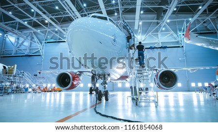 Brand New Airplane Standing in a Aircraft Maintenance Hangar while Aircraft Maintenance Engineer/ Technician/ Mechanic goes inside Cabin via Ladder/ Ramp. #1161854068