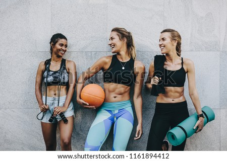 Smiling women athletes in fitness clothes relaxing after workout. Three fitness women standing outdoors holding skipping rope basketball and mat after workout. #1161894412