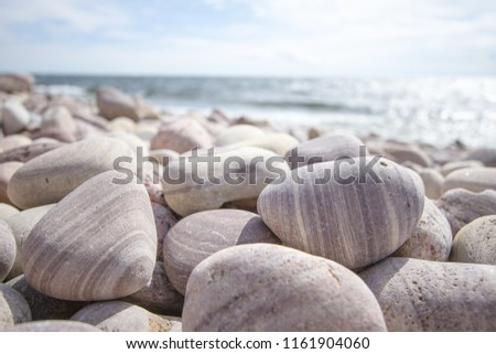 Bright light on the island stone beach with beautiful pebbles shaped by the ocean waves #1161904060
