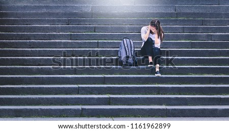 Bullying, discrimination or stress concept. Sad teenager crying in school yard. Upset young female student having anxiety. Upset victim of abuse or harassment sitting on stairs outdoors with backbag. #1161962899