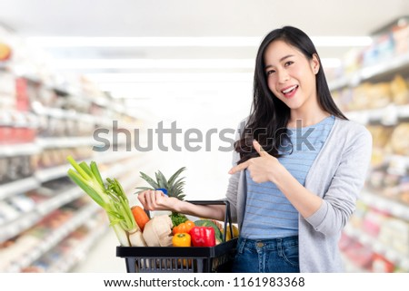 Beautiful Asian woman holding shopping basket full of vegetables and groceries in supermarket #1161983368