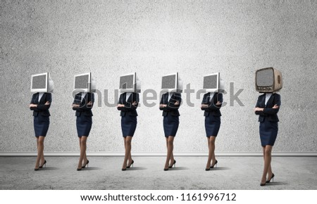 Business women in suits with monitors instead of their heads keeping arms crossed while standing in a row and one at the head with old TV in empty room against gray wall on background. #1161996712