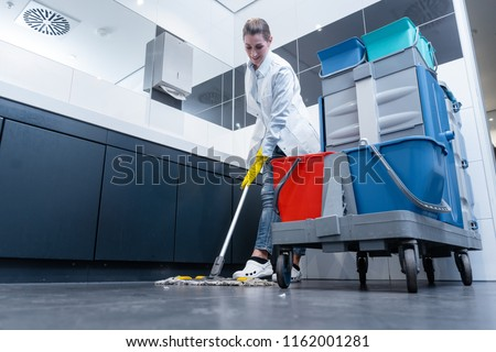 Cleaning lady mopping the floor in restroom cleaning the toilet  #1162001281