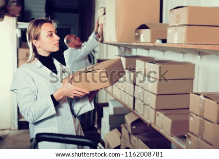 Woman worker standing with boxes in production workplace in white overalls #1162008781