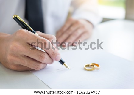 Closeup of a man Signing Contract or premarital agreement, filling petition form agreement of divorce in office at lawyer desk in court room  Conceptual of marriage. #1162024939