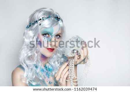 Beautiful mermaid girl in white wig curly hair. Professional makeup artist make-up, implement different images. Turn into a silver water fairy by cosmetics. Creative body art, personal vision of style #1162039474
