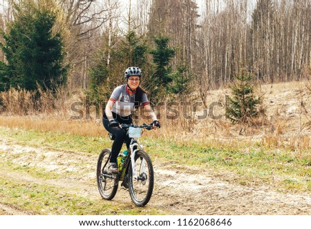 April 15, 2018, Krevo, Belarus.Beetle Trail Krevo A woman riding a bicycle on a forest path #1162068646