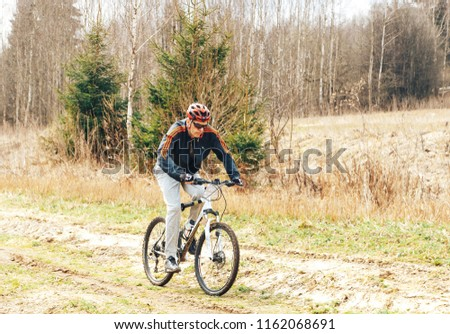 April 15, 2018, Krevo, Belarus.Beetle Trail Krevo A man riding a bicycle on a forest path #1162068691