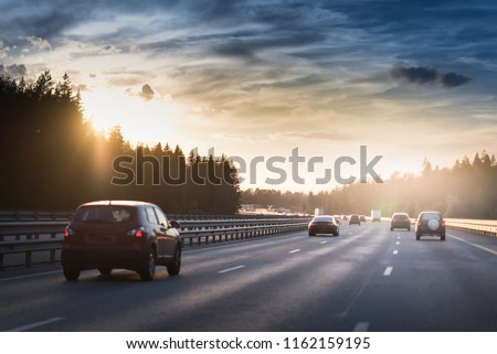 Highway traffic in sunset. minivan on the asphalt road with metal safety barrier or rail. Pine forest on the background #1162159195