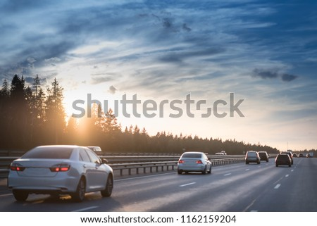 Highway traffic in sunset. minivan on the asphalt road with metal safety barrier or rail. Pine forest on the background #1162159204