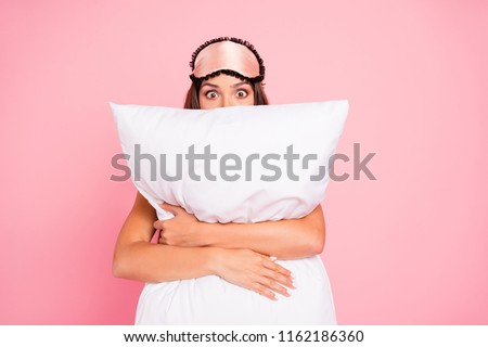 Young gorgeous shocked lady wearing eye mask, hugging pillow, hiding. Isolated over pink pastel background #1162186360