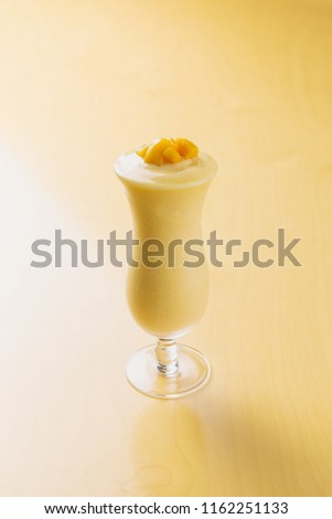 mango smoothie on a wooden table #1162251133