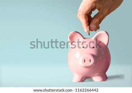 Hand putting coin to piggy bank Royalty-Free Stock Photo #1162266442