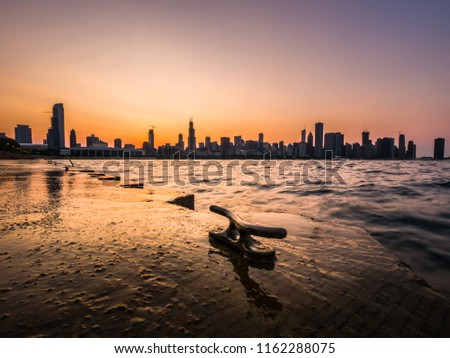 Chicago skyline picture during a beautiful sunset with purple and orange sky above and building silhouettes on the horizon with rippling waves of Lake Michigan and metal boat cleat in the foreground.