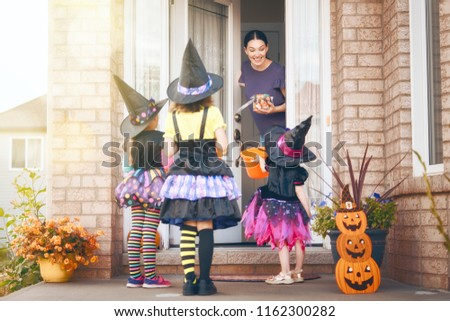 Happy family celebrating Halloween! Young mom treats children with candy. Funny kids in carnival costumes. #1162300282