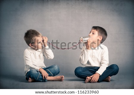 Young brothers talking with tin can telephone on grunge background. Royalty-Free Stock Photo #116233960