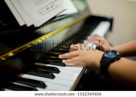 selective focus to hands of boy put black watch to play the piano with music notation.  There are musical instrument for learning music. #1162369606
