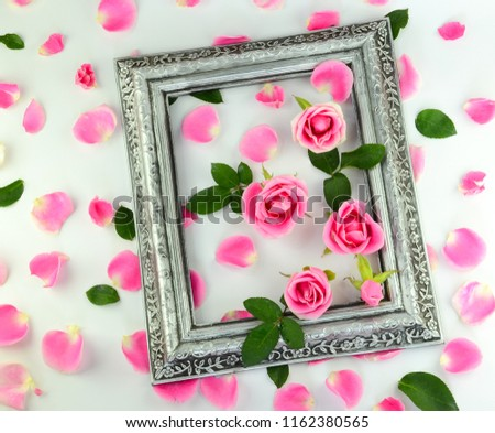 Pink roses bloom in an ancient silver frame and flower petals placed on a white background.