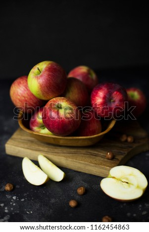 Pink lady apples in wooden bowl on wood board at black background #1162454863