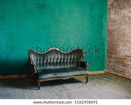 classic interior in dark green colors. vintage velvet sofa near emerald wall. Armrest of luxurious green sofa, close-up. Luxury vintage green couch in the room. Antique wood sofa couch. #1162458691