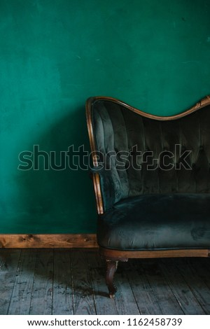 classic interior in dark green colors. vintage velvet sofa near emerald wall. Armrest of luxurious green sofa, close-up. Luxury vintage green couch in the room. Antique wood sofa couch. #1162458739