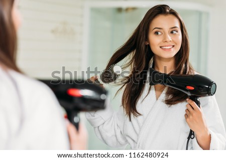 happy young woman drying hair at mirror in bathroom  #1162480924