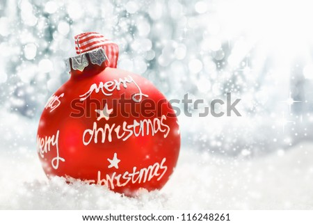 Beautiful atmospheric Merry Christmas greeting card with a red decorated bauble bearing the words Merry Christmas on a bed of snow with the sun bouncing off falling snowflakes with copyspace