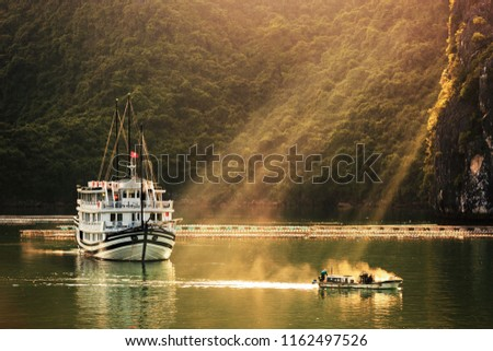 boat in ray light, sunset in Ha Long bay,  A corner of Ha Long Bay, view from above. Halong bay is a UNESCO World Heritage Site and popular travel destination in Quang Ninh Province Royalty-Free Stock Photo #1162497526