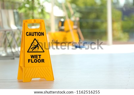 Safety sign with phrase Caution wet floor and blurred mop bucket on background. Cleaning service Royalty-Free Stock Photo #1162516255