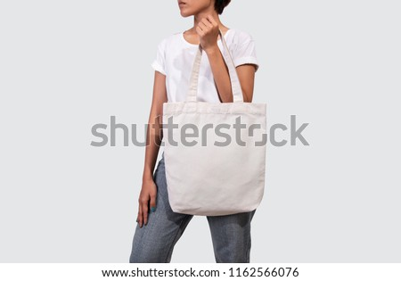 Girl is holding bag canvas fabric for mockup blank template isolated on gray background.  #1162566076
