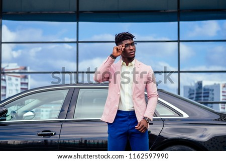 successful businessman handsome African American dreadlocks man in a stylish suit in pink jacket and glasses standing in front of a cool new black car on the street #1162597990