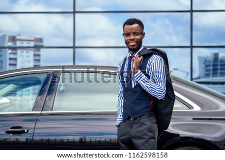 successful businessman handsome African American man in a stylish suit in gray jacket and glasses standing in front of a cool new black car on the street #1162598158