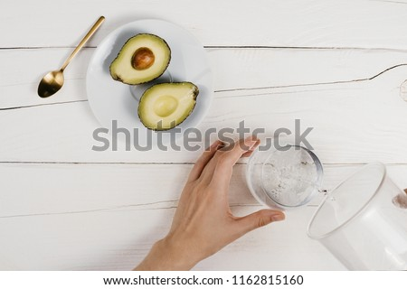 Flatlay with fresh ripe cut avocado halves and woman's hand pouring clean water in a glass on wooden white table, healthy eating concept #1162815160