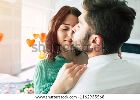 Tender kiss. Close up photo of Handsome young man is kissing his beloved cute woman in date romantic day #1162935568
