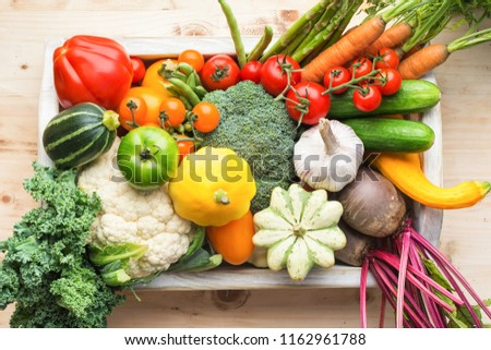 Fresh organic vegetables in a white tray on wooden pine table, top view, selective focus #1162961788
