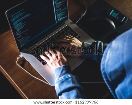 overhead hacker in the hood working with laptop and mobile phone typing text in dark room #1162999966