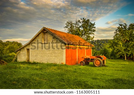 Old red tractor and garage. Agriculture. Farm machinery. Dramatic sky. #1163005111