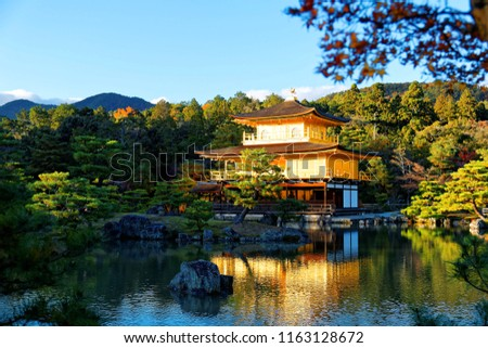 Fall scenery of Kinkakuji, a famous Zen Buddhist temple in Kyoto, Japan, with the majestic Golden Pavilion glittering under blue clear sky & reflected in the peaceful lake water on a sunny autumn day #1163128672