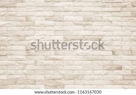 Cream and white brick wall texture background. Brickwork or stonework flooring interior rock old pattern clean concrete grid uneven bricks design stack. #1163167030