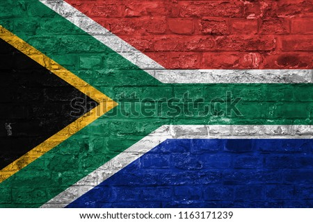 Flag of South Africa over an old brick wall background, surface