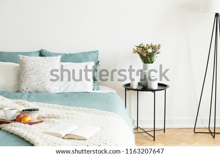 Close-up of a bed with pale sage green and white linen, pillows and a blanket in a sunny bedroom interior. A round black metal side table with vases and flowers beside the bed. Real photo #1163207647