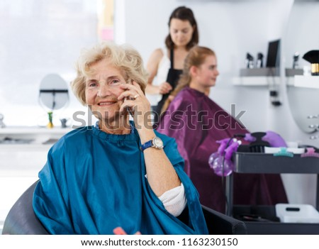 Portrait of elderly female client waiting for hair styling in modern hair salon, talking on phone