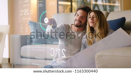A couple sitting on the sofa controls all the functions of the house such as wi-fi, heating, lighting, television through holography. Concept of, home automation, automations, future, technology. #1163300440